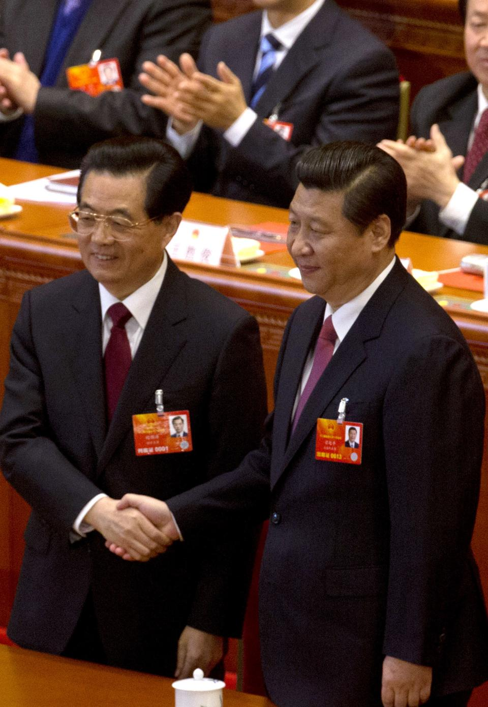 Former Chinese President Hu Jintao, left, poses with his sucessor Xi Jinping after Xi was elected at a plenary session of the National People's Congress held at the Great Hall of the People in Beijing Thursday, March 14, 2013. (AP Photo/Ng Han Guan)