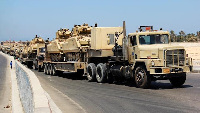 FILE - In this Thursday, Aug. 9, 2012 file photo, army trucks carry Egyptian tanks in a military convoy in El Arish, Egypt's northern Sinai Peninsula. On Monday, May 20, 2013 Egyptian officials said dozens of military and police armored vehicles have crossed into Sinai, beefing up the security presence in the volatile peninsula five days after suspected militants kidnapped six policemen and a border guard there. (AP Photo, File)