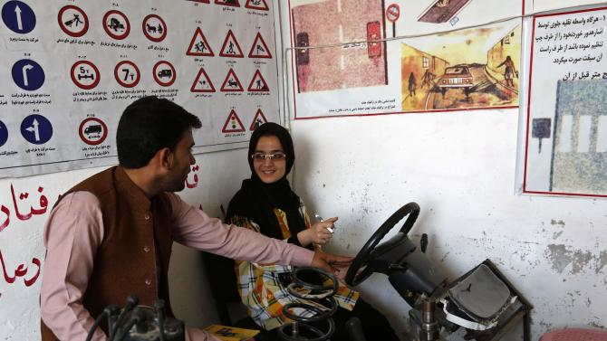 Tahmina talks to her instructor during a practical lesson at a driving school in Kabul