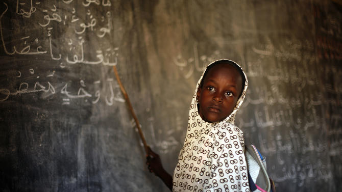 A Malian schoolgirl listens to her teacher as schools reopen in Gao, northern Mali, Monday Feb. 18, 2013. (AP Photo/Jerome Delay)