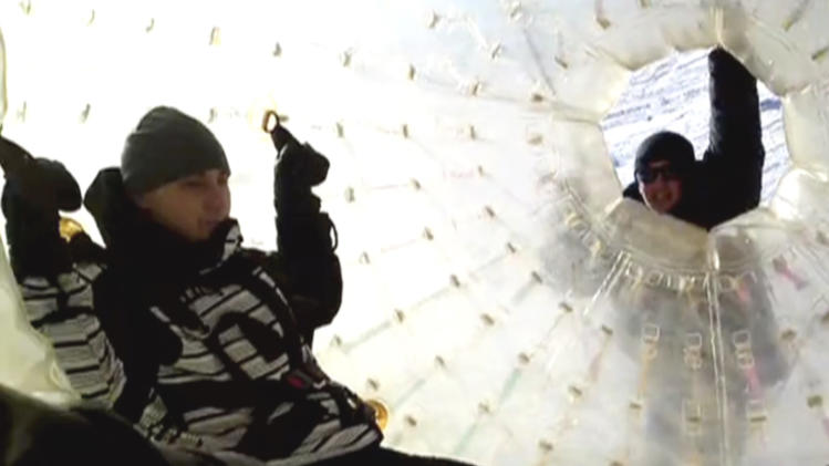 In this frame grab made Wednesday Jan. 9, 2013, taken from APTN video provided by Yekaterina Achkasova, as her husband Denis Burakov, left, inside the large plastic ball called a zorb, with another man, before tragedy struck on Thursday, Jan. 3, 2013,  at a winter sports venue at Dombai in the Caucasus Mountains of southern Russia.  What was supposed to be a thrilling ride down a ski slope inside a giant inflatable ball has ended in tragedy when the zorb veered off course and sailed over a cliff, killing Denis Burakov and leaving the other man badly injured. (AP Photo/Family photo provided by Yekaterina Achkasova, APTN)