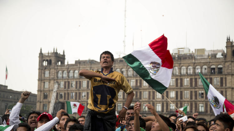 Mexico soccer fans sing the national anthem as they watch their team's 2014 World Cup match with Croatia on giant television screens in Mexico City's main square, the Zocalo, Monday, June 23, 2014. Needing only a tie to advance to the second round of the World Cup for a sixth straight time, Mexico is bound to please its fans. (AP Photo/Moises Castillo)