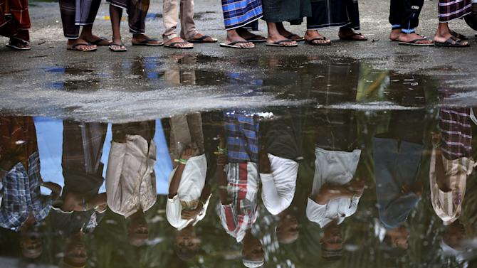 Rohingya migrants who arrived in Indonesia last week by boat are reflected in a puddle while waiting for breakfast at a temporary shelter in Aceh Timur regency, near Langsa in Indonesia's Aceh Province