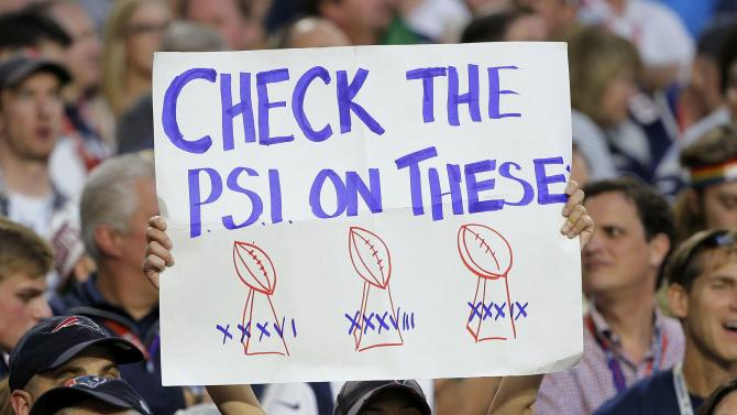A fan holds up a sign referring to the air pressure in footballs on the Vince Lombardi Trophy during the NFL Super Bowl XLIX football game between the Seattle Seahawks and the New England Patriots in Glendale