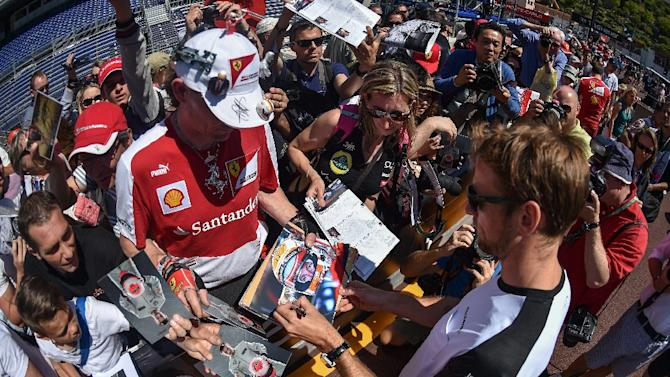 McLaren Honda's British driver Jenson Button signs autographs ahead of the Monaco Formula One Grand Prix in Monte Carlo on May 22, 2015