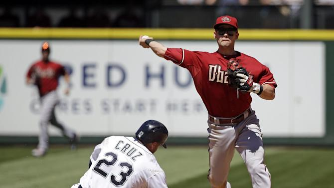 Arizona Diamondbacks second baseman Chris Owings, right, throws to first after forcing out Seattle Mariners' Nelson Cruz at second base in the fourth inning of a baseball game Wednesday, July 29, 2015, in Seattle. Mark Trumbo was safe at first on a fielder's choice. (AP Photo/Elaine Thompson)