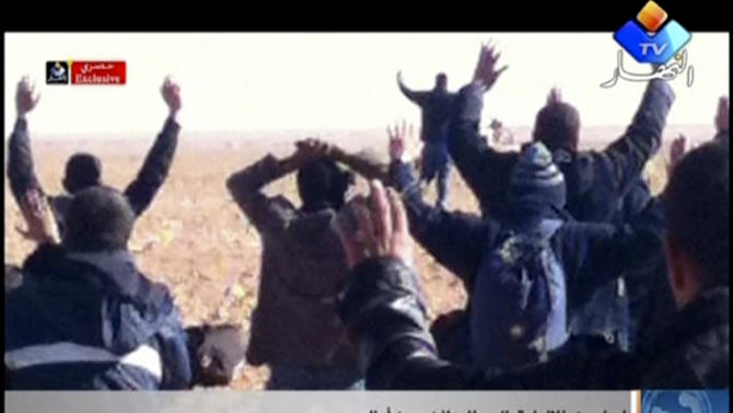 """In this image made from video, a group of people believed to be hostages kneel in the sand with their hands in the air at an unknown location in Algeria. An Algerian security official says de-mining squads searching for explosives found """"numerous"""" bodies Sunday, Jan. 20, 2013 at a gas refinery where Islamic militants took dozens of foreign workers hostage. (AP Photo/Ennahar TV) ALGERIA OUT, TV OUT"""