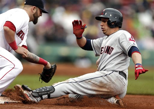 Cleveland Indians' Asdrubal Cabrera, right, slides safely back to first base after rounding on a single as Boston Red Sox first baseman Mike Napoli takes the throw during the seventh inning of a baseb