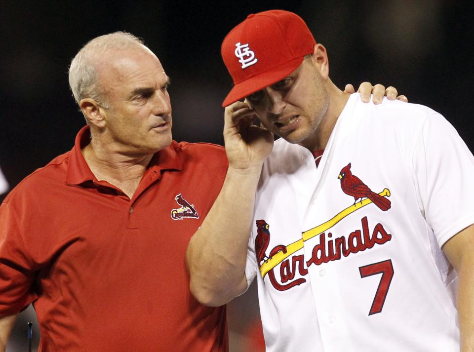 St. Louis Cardinals trainer Barry Weinberg, left, helps Cardinals left fielder Matt Holliday as Holliday leaves a baseball game holding his ear during the eighth inning against the Los Angeles Dodgers Monday, Aug. 22, 2011, in St. Louis. (AP Photo/Jeff Roberson)