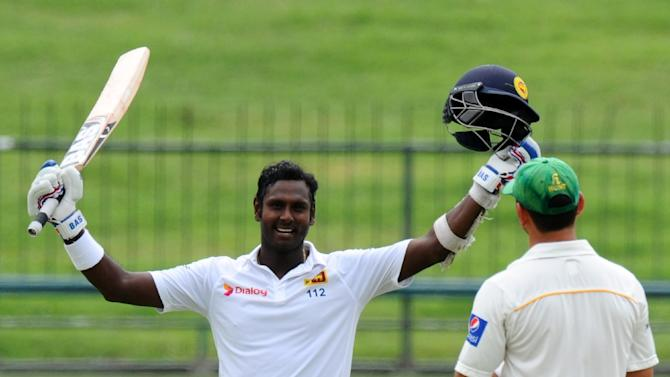 Sri Lanka captain Angelo Mathews raises his bat and helmet in celebration after scoring a century during the fourth day of the third and final Test against Pakistan in Pallekele on July 6, 2015