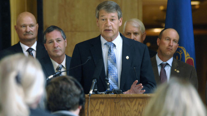 "FILE - In this June 29, 2015, file photo, North Dakota Attorney Gen. Wayne Stenehjem, center, announces that the state is joining attorneys general from other states in a lawsuit against the Environmental Protection Agency (EPA) and the U.S. Army Corps of Engineers over the EPA's new rule defining ""Waters of the United States"" under the Clean Water Act, at the state Capitol in Bismarck. North Dakota Agriculture Commissioner Doug Goehring, second from left, looks on. (Mike Mccleary/The Bismarck Tribune via AP) MANDATORY CREDIT"