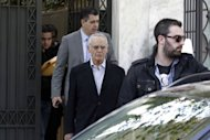 Former Greek minister Akis Tsochatzopoulos (centre) is taken from his home in Athens to a prosecutor by Finance Ministry's anti-fraud squad officials, on April 11, 2012