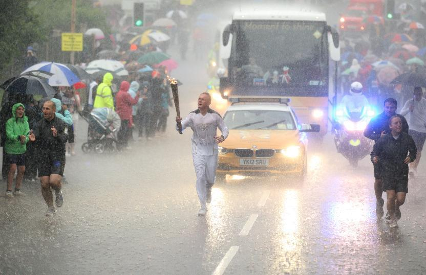 FILE - This Thursday June 28, 2012 file photo made available by LOCOG shows Glenn Chambers carrying the Olympic Flame on the Torch Relay leg between Edwinstowe and Mansfield, near Lincoln, England, during a heavy downpour, on Day 41 of the London 2012 Olympic Torch Relay. (AP Photo/LOCOG, Chris Radburn, File)