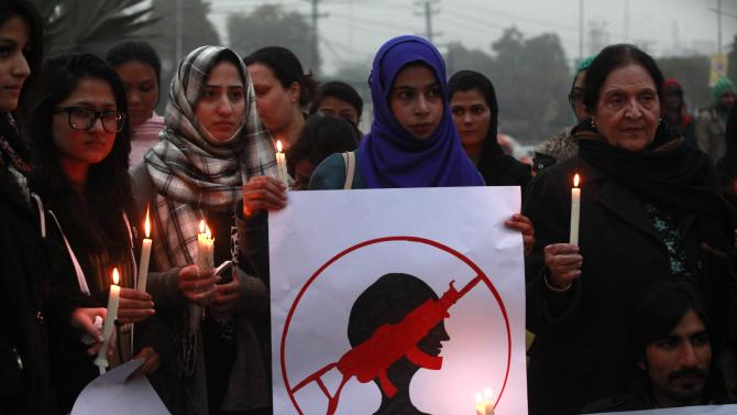 People hold candles and a sign to condemn the Taliban attack on the Army Public School in Peshawar, during a rally in Lahore