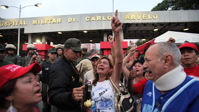 Supporters of Venezuela's President Hugo Chavez react to the news that that Chavez has died, as they gather outside the military hospital where Chavez was being treated in Caracas, Venezuela, Tuesday, March 5, 2013. Venezuela's Vice President Nicolas Maduro announced that Chavez died on Tuesday at age 58 after a nearly two-year bout with cancer. During more than 14 years in office, Chavez routinely challenged the status quo at home and internationally. He polarized Venezuelans with his confrontational and domineering style, yet was also a masterful communicator and strategist who tapped into Venezuelan nationalism to win broad support, particularly among the poor. (AP Photo/Fernando Llano)