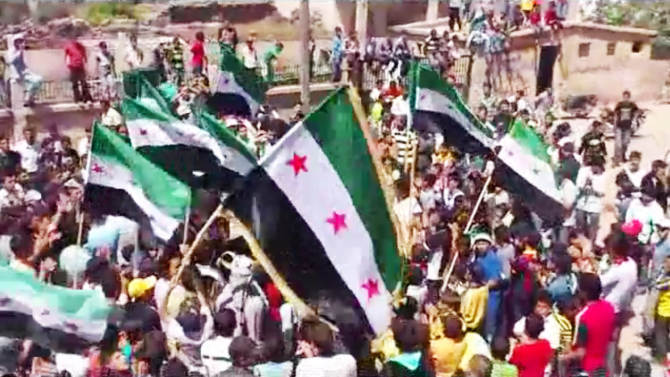 In this image made from amateur video released by the Shaam News Network and accessed Wednesday, May 2, 2012, protesters carry Syrian revolutionary flags during a demonstration in Daraa, Syria. Syrian activists said government forces clashed with army defectors in the country's north on Wednesday, causing casualties and further enflaming an area near the Turkish border where rebel fighters have tried to seize territory. (AP Photo/Shaam News Network via AP video) TV OUT, THE ASSOCIATED PRESS CANNOT INDEPENDENTLY VERIFY THE CONTENT, DATE, LOCATION OR AUTHENTICITY OF THIS MATERIAL