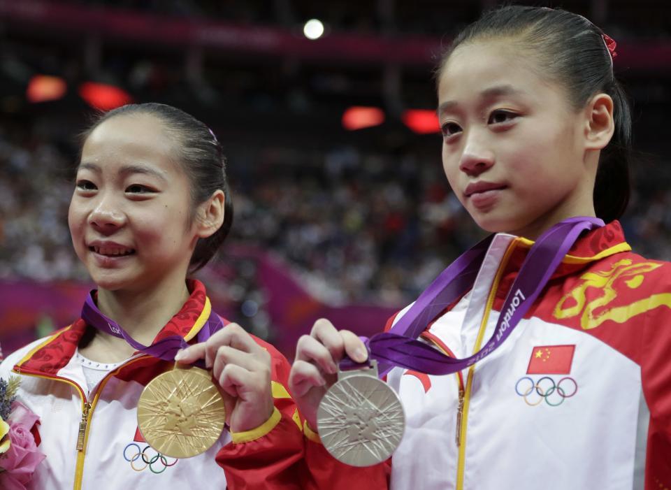Chinese gold medallist gymnast Deng Linlin, left, and silver medallist China's Sui Lu display their medals for the balance beam during the artistic gymnastics women's apparatus finals at the 2012 Summer Olympics, Tuesday, Aug. 7, 2012, in London. (AP Photo/Gregory Bull)