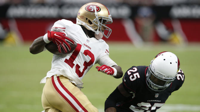 San Francisco 49ers wide receiver Steve Johnson (13) tries to avoid Arizona Cardinals cornerback Jerraud Powers (25) during the second half of an NFL football game, Sunday, Sept. 21, 2014, in Glendale, Ariz. (AP Photo/Ross D. Franklin)