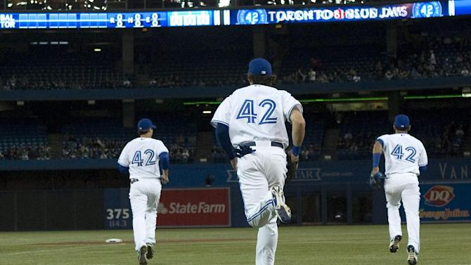 Toronto Blue Jays players wear No. 42 jerseys honoring Jackie Robinson as they take to the field ahead of their baseball game against the Baltimore Orioles in Toronto, Sunday April 15 , 2012. (AP Photo/The Canadian Press, Chris Young)