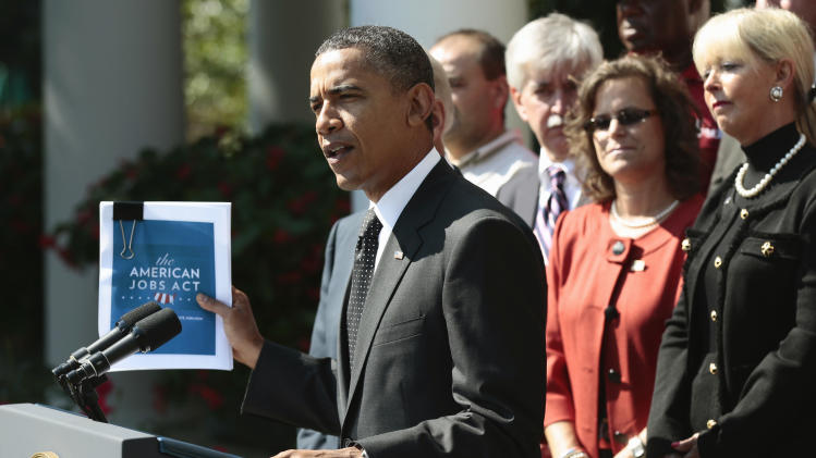 President Barack Obama holds up his proposed American Jobs Act legislation while making a statement in the Rose Garden of the White House in Washington, Monday, Sept., 12, 2011. (AP Photo/Pablo Martinez Monsivais)