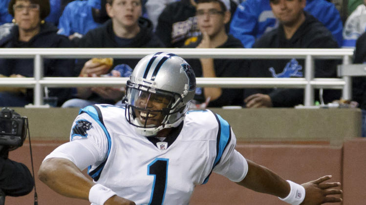 Carolina Panthers quarterback Cam Newton celebrates his 11-yard touchdown run in the second quarter of an NFL football game against the Detroit Lions in Detroit, Sunday, Nov. 20, 2011. (AP Photo/Rick Osentoski)