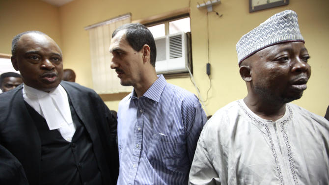 Chris Uche, left, lawyer of Iranian, Azim Aghajani, centre, and Nigerian, Usman, Abbas, right,  speaks, as  the waits for a court verdict at the Federal High Court, in Lagos, Nigeria, Monday, May 13, 2013. . An Iranian and his Nigerian accomplice were sentenced to five years in prison Monday over a plot they orchestrated to smuggle a shipment of military-grade weapons including mortar rounds into West Africa. Both Azim Aghajani and his accomplice Usman Abbas Jega pleaded for leniency in the hearing, which saw Justice Okechukwu J. Okeke avoid giving the men a maximum sentence of life in prison. The two men already have served more than two years in prison waiting for trial, time which will count toward their release. (AP Photos/Sunday Alamba)