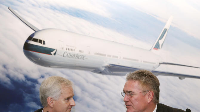 Chairman of Cathay Pacific Airways, Christopher Pratt, right, chats with Chief Executive John Slosar at a company result announcement in Hong Kong Wednesday, Aug. 8, 2012. Cathay Pacific Airways Ltd., Hong Kong's biggest airline, posted its biggest first-half loss in a decade on Wednesday because of persistently high fuel prices, the global economic slump and poor air cargo demand. (AP Photo/Kin Cheung)