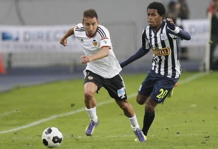 Pereira of Spain's Valencia CF fights for the ball with Landauri of Peru's Alianza Lima during their Copa Euroamericana soccer match in Lima