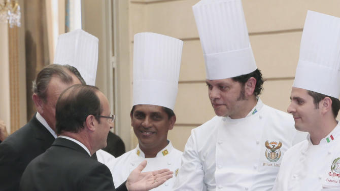 """French President Francois Hollande, left, shakes hand with Hilton Little, 2nd right, chef at the South African president residence during a reception at the Elysee palace in Paris, Tuesday July 24, 2012, following the """"Chef des Chefs Club"""" (CCC) international meeting. (AP Photo/Jacques Demarthon, Pool)"""