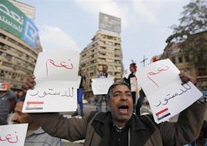 A supporter of Egypt's army chief and defense minister Sisi holds signs during a protest in Cairo