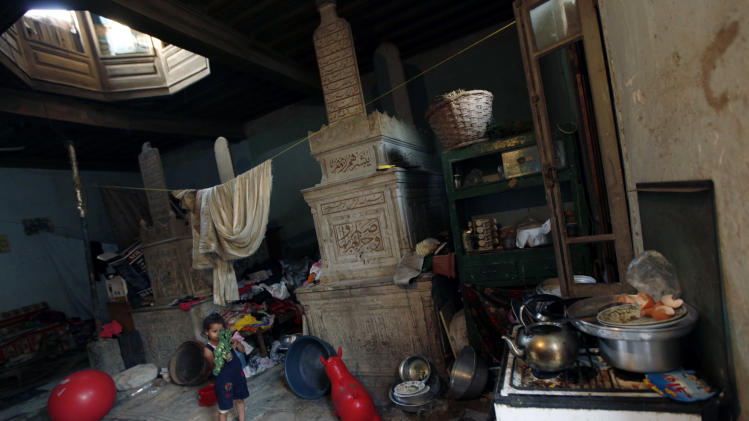In this photo taken on Monday, May 21, 2012, a girl plays next to tombs in a room where her family lives in a necropolis called the City of the Dead, in Cairo, Egypt. The City of the Dead is a 4 mile (6.4 kilometer) long necropolis where thousands of Egyptians are forced to live and work alongside graves due to the scarcity of housing in the capital. (AP Photo/Khalil Hamra)