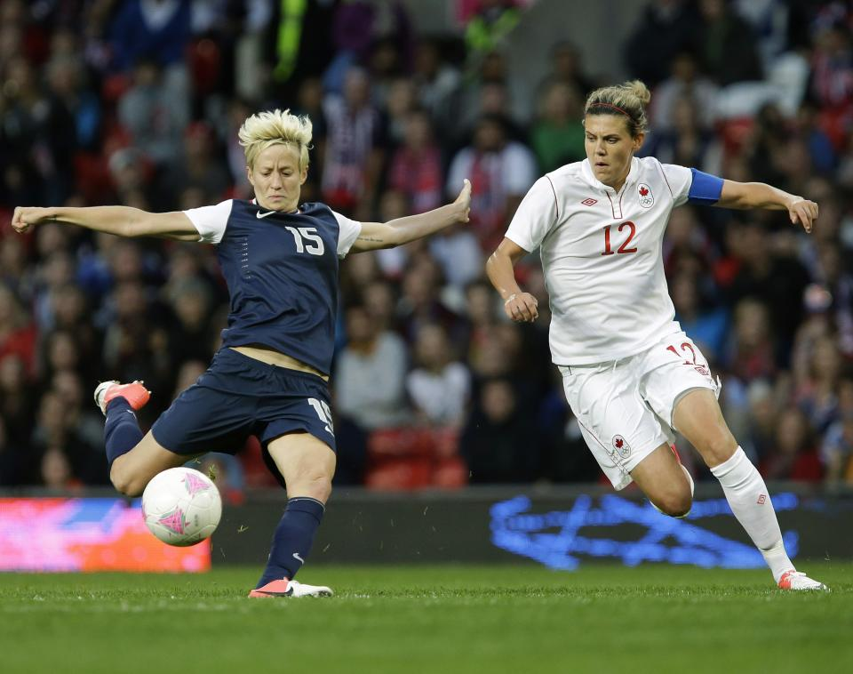 United States' Megan Rapinoe, left, prepares to kick the ball against Canada's Christine Sinclair, right, during their semifinal women's soccer match at the 2012 London Summer Olympics, in Manchester, England, Monday, Aug. 6, 2012. (AP Photo/Hussein Malla)