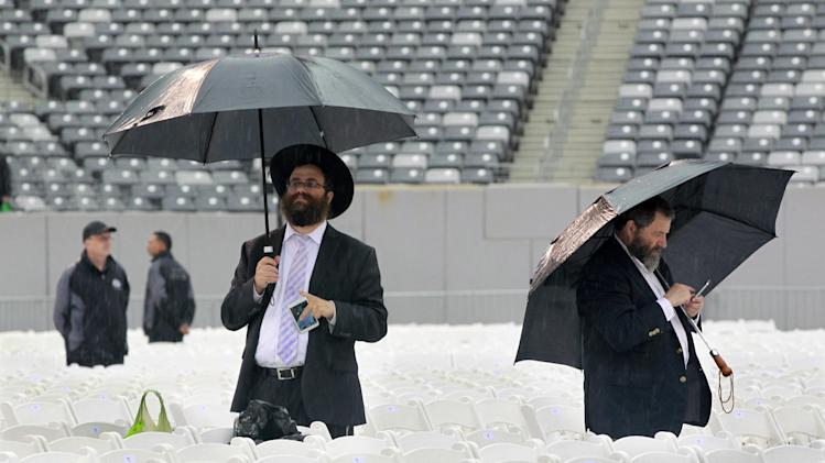 Men stand in the rain at MetLife stadium in East Rutherford, N.J, Wednesday, Aug. 1, 2012, as they wait for the start of the celebration Siyum HaShas. The Siyum HaShas, marks the completion of the Daf Yomi, or daily reading and study of one page of the 2,711 page book. The cycle takes about 7½ years to finish.This is the 12th put on my Agudath Israel of America, an Orthodox Jewish organization based in New York. Organizers say this year's will be, by far, the largest one yet. More than 90,000 tickets have been sold, and faithful will gather at about 100 locations worldwide to watch the celebration. (AP Photo/Mel Evans)