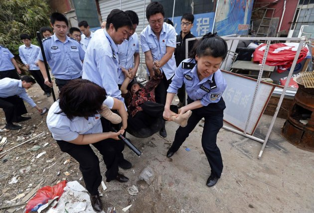 Policemen and judicial officials carry a woman away as she resists the demolition of her houses in Qingdao