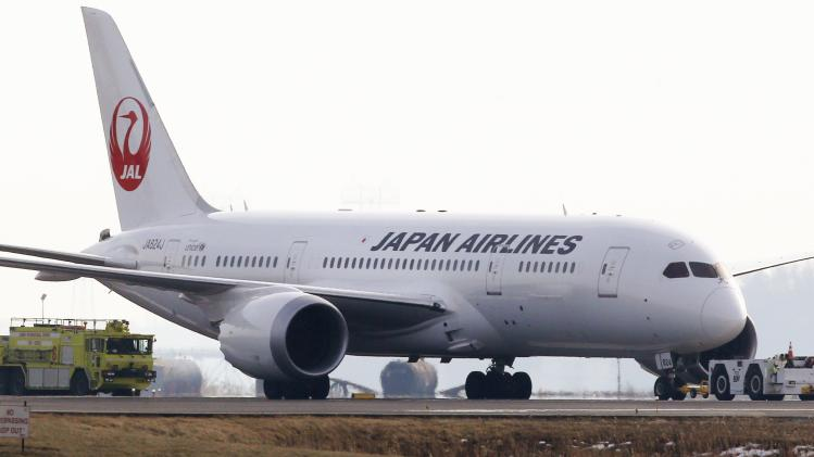 A Japan Airlines 787 is escorted by a fire engine as it is towed away from the runways at Logan Airport in Boston, Tuesday, Jan. 8, 2013. Officials say crews have contained a fuel leak from the outbound Japan Airlines flight to Tokyo in the second incident involving the airline at Logan in two days. (AP Photo/Charles Krupa)