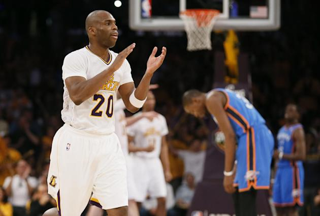 Los Angeles Lakers shooting guard Jodie Meeks, left, celebrates late in the fourth quarter as Oklahoma City Thunder small forward Kevin Durant, right, reaxts during an NBA basketball game in Los Angel