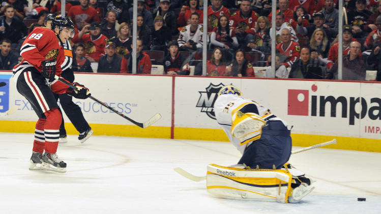 Chicago Blackhawks' Patrick Kane (88) shoots the puck past the Nashville Predators' Pekka Rinne during the second period of an NHL hockey game on Friday, April 19, 2013, in Chicago. (AP Photo/Jim Prisching)