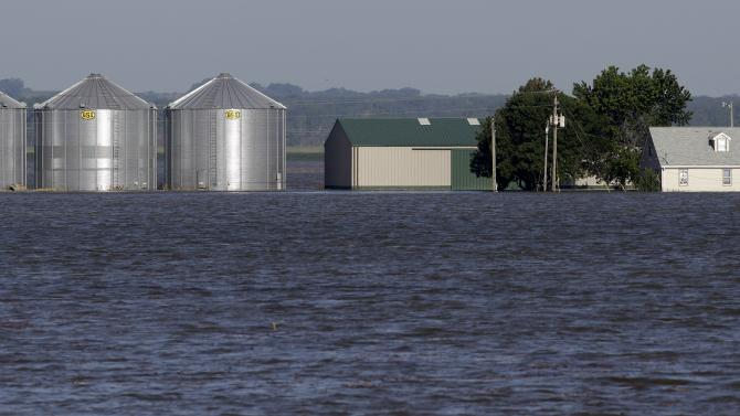 A farmhouse and buildings sit surrounded by flood waters from the nearby Missouri River, Wednesday, June 15, 2011, in Hamburg, Iowa. The water level continues to rise and officials say that it should crest sometime later this week. (AP Photo/Charlie Neibergall)