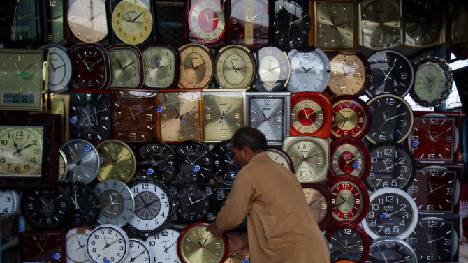 A Pakistani vendor adjusts a wall clock displayed at his stall for sale at a weekly bazaar in Islamabad, Pakistan, Sunday, Oct. 19, 2014. (AP Photo/Anjum Naveed)