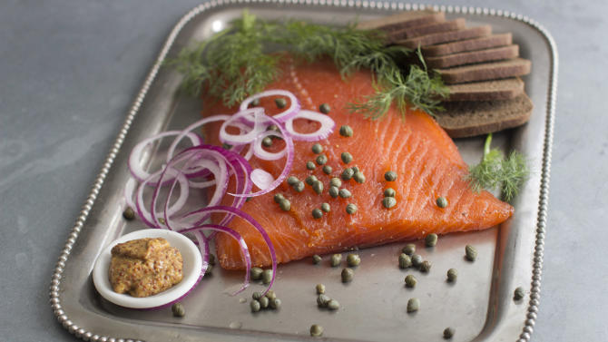 This Aug. 18, 2014 photo shows do it yourself cured salmon in Concord, N.H. Gravlax , as cured salmon is known by its Nordic name, generally is made by dry-curing fillets of salmon in a blend of sugar, kosher salt, fresh dill and a variety of other seasonings. The process extracts moisture from the flesh of the salmon, producing a smooth, yet meaty texture and a wonderfully salty-sweet flavor. (AP Photo/Matthew Mead)