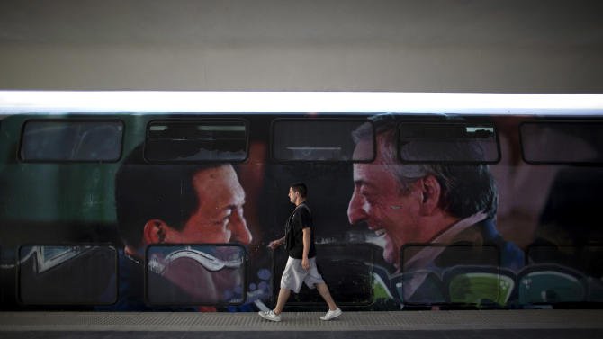 In this Jan. 28, 2013 photo, a passenger walks past a train wagon covered with the faces of Argentina's late President Nestor Kirchner, right, and Venezuela's President Hugo Chavez at the Once train station in Buenos Aires, Argentina. Nearly a year after a train crash killed 51 people and injured 800 others on Feb. 22, 2012, exposing systemic corruption and other failures in Argentina's transportation systems, the victims' families and other passengers are as angry as ever over a litany of promised improvements and safety measures that have not been made. (AP Photo/Natacha Pisarenko)