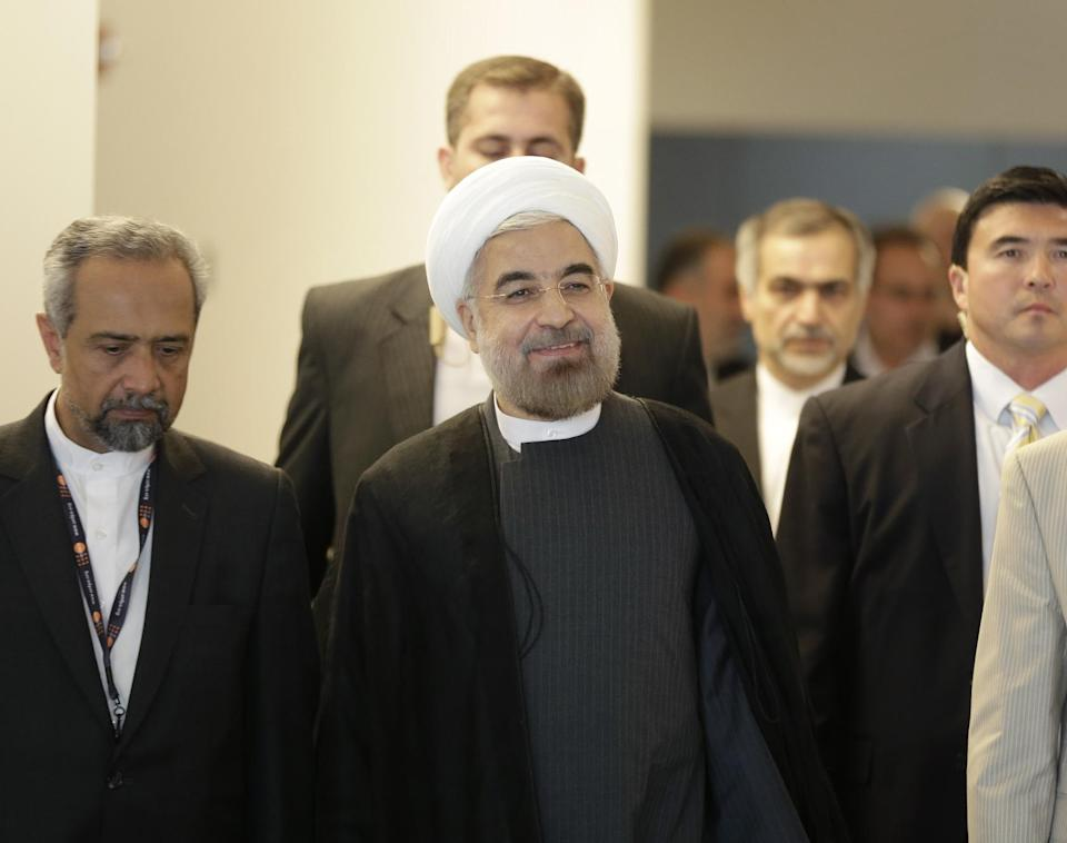 Iranian President Hassan Rouhani, center, walks through the hallway during the 68th session of the General Assembly at United Nations headquarters, Thursday, Sept. 26, 2013. (AP Photo/Seth Wenig)