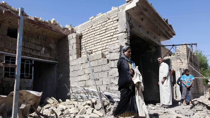 An Iraqi woman stands in rubble at the scene of a car bomb attack in the town of Taji, about 12 miles (20 kilometers) north of Baghdad, Iraq, Sunday, Sept. 30, 2012. A rapid-fire series of explosions in Baghdad while Iraqis were going to work on Sunday morning, killed and wounded scores of people, police said. (AP Photo/Hadi Mizban)