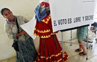 Taraumara indigenous women in traditional clothes cast their votes at a polling station in the northern border city of Ciudad Juarez, Mexico during elections. Voters, exhausted by violence, seem prepared to bring the Institutional Revolutionary Party (PRI), which ran the country for seven decades, back to office