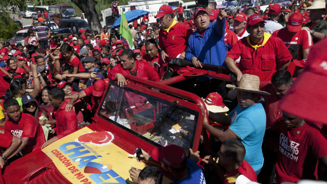 Venezuela's President Hugo Chavez greets supporters from the top of a vehicle during a campaign caravan from Barinas to Caracas, in Sabaneta, Venezuela, Monday, Oct. 1, 2012. Venezuela's presidential election is scheduled for Oct. 7. (AP Photo/Rodrigo Abd)