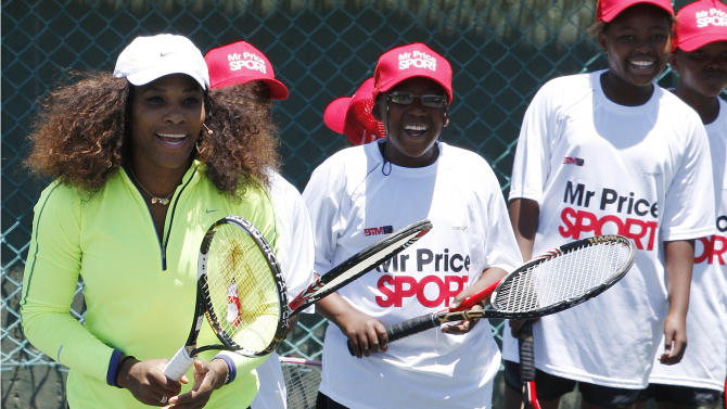 Serena Williams of the United States, left, plays as tennis students participate in a 'Breaking the Mould' development tennis clinic at the Arthur Ashe Academy in Soweto, South Africa, on Saturday Nov. 3, 2012.  Serena and sister Venus arrived in Johannesburg on Saturday and are scheduled to play an exhibition match togehter, as well as conducting some tennis sports clinics for children and adults.(AP Photo/Themba Hadebe)