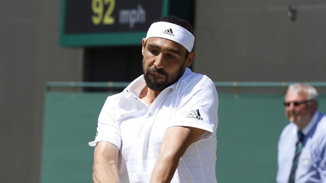 Marcos Baghdatis of Cyprus makes a return to David Goffin of Belgium during their singles match at the All England Lawn Tennis Championships in Wimbledon, London, Friday July 3, 2015. (AP Photo/Alastair Grant)
