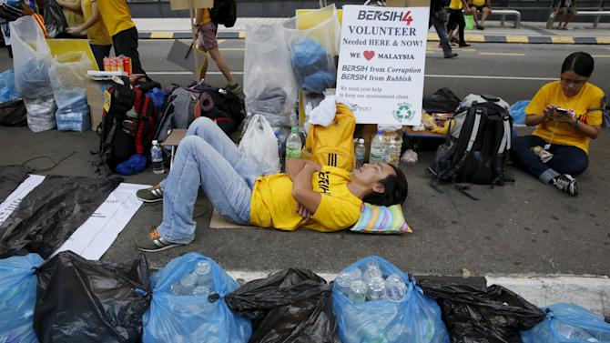 "Protester sleeps amongst sorted recycling in plastic bags during a rally organised by pro-democracy group ""Bersih"" in Malaysia's capital city of Kuala Lumpur"