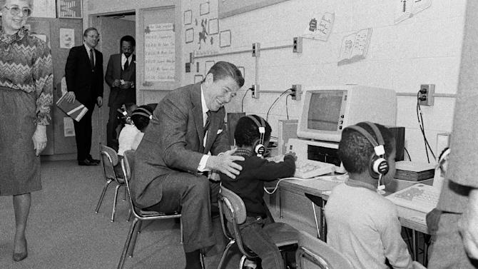 "FILE - In this March 12, 1984, file photo, President Ronald Reagan gets some instructions on computer operations while visiting the Congress Heights Elementary School in Washington. The White House has taken the school as one of their projects in its operation. U.S. students are falling behind their international rivals. Young people aren't adept at new technology. America's economy will suffer if schools don't step up their game. ""A Nation at Risk,"" the report issued 30 years ago by Reagan's Education Department, was meant as a wake-up call for the country. It spelled out where the United States was coming up short in education and what steps could be taken to avert a crisis. But its warnings still reverberate today, with 1 in 4 Americans failing to earn a high school degree on time and the U.S. lagging other countries in the percentage of young people who complete college. (AP Photo/Scott Applewhite, File)"