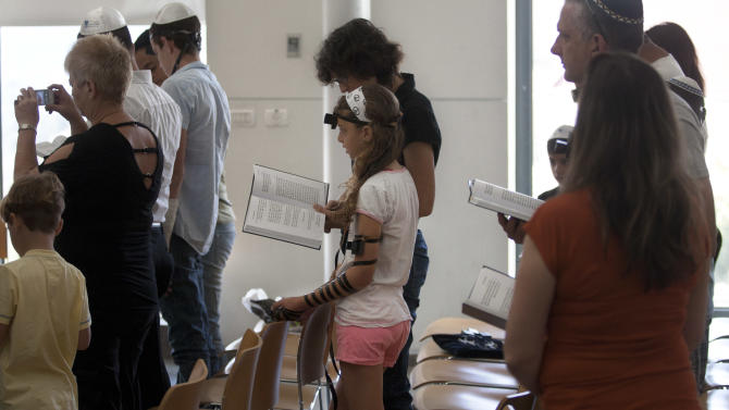In this Thursday, June 14, 2012 photo an Israeli children pray with their families in a reformist Jewish synagogue, in Mevasseret Zion near Jerusalem.   Israel's attorney general recently announced that a group of 15 non-Orthodox rabbis who answer a certain criteria will begin to receive government funding like some 2,000 of their Orthodox and ultra-Orthodox brethren.(AP Photo/Sebastian Scheiner)